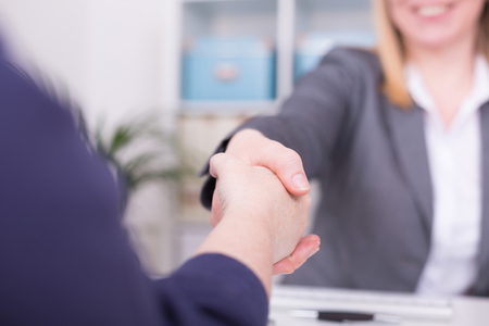 Two women at the office having an agreement and shaking hands.