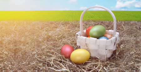 Colorful easter eggs in a wooden basket.