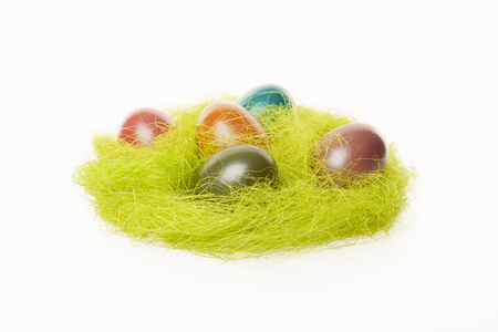 Easter nest with colorful eggs isolated on white background.