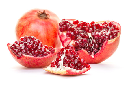 A whole pomegranate disassembled into parts isolated on white background. Healthy red food, diet and organic fair trade concept.