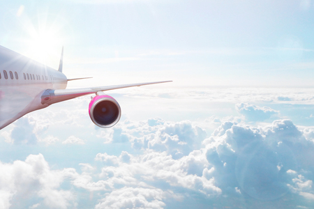 Airplane flying high above the clouds. Transportation, vacation and travel concept.