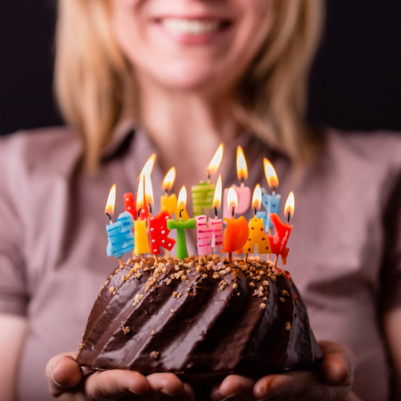 Mother holding a birthday cake with colorful candles. Birthday, party and family concept.