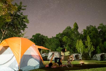 A camping tent glows under a night sky at khao yai
