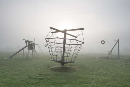 A deserted children's playground on a cold and foggy morning.