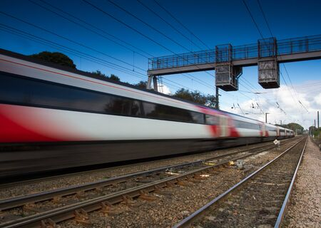 treno espresso: A speeding passenger express train that is blurred and underneath electric wires.