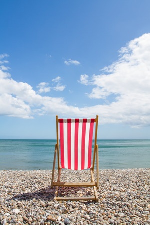 red pebble: An empty, red and white striped Deckchair facing the ocean on a deserted pebble beach. Stock Photo