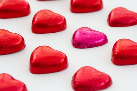 'odd one out': Valentines Day chocolate shaped hearts lined up in rows on an isolated white background.
