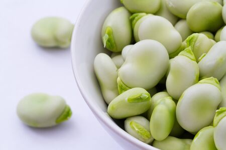 glut: A close up image of a bowlful of broad beans on an isolated white background.