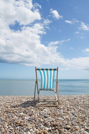 recuperate: A blue and white Deckchair facing the ocean on a deserted pebble beach.