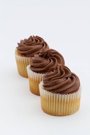 overeat: Three chocolate cupcakes in a row on an isolated white background. Portrait orientation with copy space. Stock Photo