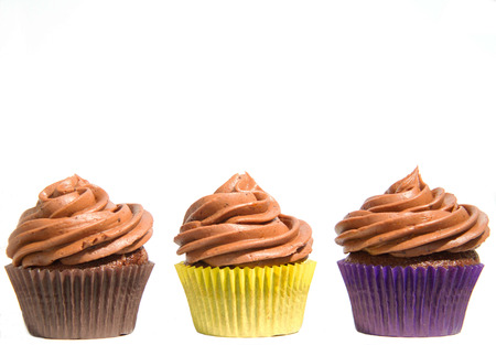 Three chocolate cupcakes in colourful cases and lined up in a row from left to right. Isolated white background. Stock Photo