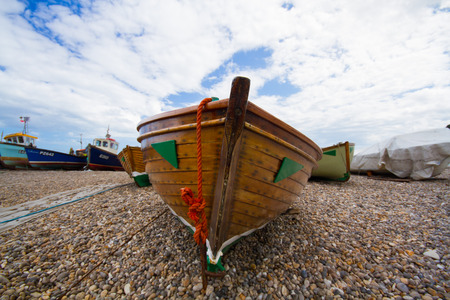 beached: Beached, wooden fishing boats sitting on a pebble beach. Stock Photo