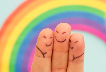fingers: Fingers with characters drawn on them to create three friends hugging in front of a rainbow.
