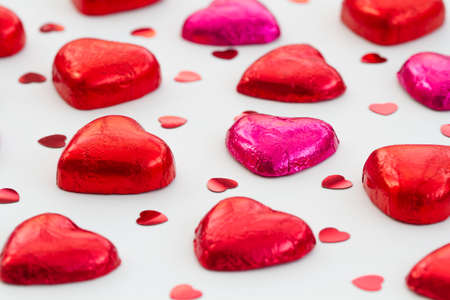 scattered in heart shaped: Heart Shaped Valentine Chocolates scattered over a white, isolated background.