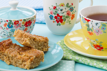Afternoon tea or high tea of cake and a cup of tea in floral crockery. Stock Photo