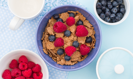 A healthy breakfast of cereal, raspberries and blueberries for an energy boost at the start of the day. View from above looking down onto the table. Stock Photo