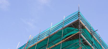 high rise building: A high rise building surrounded by scaffold during construction work. Stock Photo