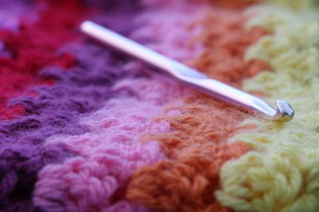 crocheted: A crochet hook on a crocheted, stripy blanket. Stock Photo