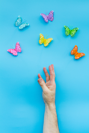 grasp: A hand and arm reaching for some butterflies on a blue background. Stock Photo