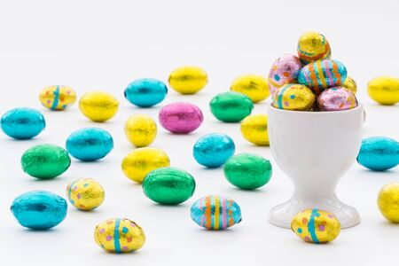 scattered on white background: A white egg cup filled with colourful, chocolate Easter eggs on an isolated white background. Lots of Easter eggs scattered over a white background.