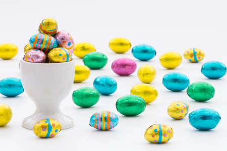 egg cup: A white egg cup filled with colourful, chocolate Easter eggs on an isolated white background. Lots of Easter eggs scattered over a white background.