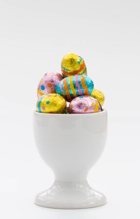 egg cup: A white egg cup filled with colourful, chocolate Easter eggs on an isolated white background.