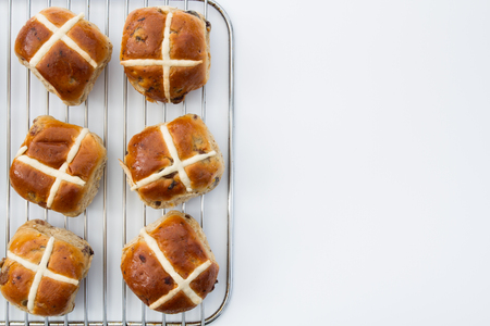 overeat: Freshly baked, Easter, hot cross buns on an isolated white background. View from above, looking down.