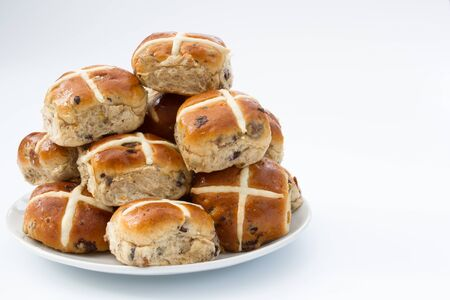 A plate full of freshly baked, Easter, hot cross buns on an isolated white background.