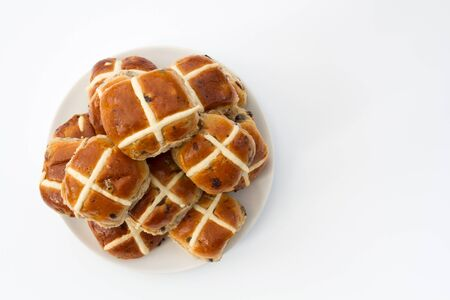 buns: A plate full of freshly baked, Easter, hot cross buns on an isolated white background. View from above looking down.