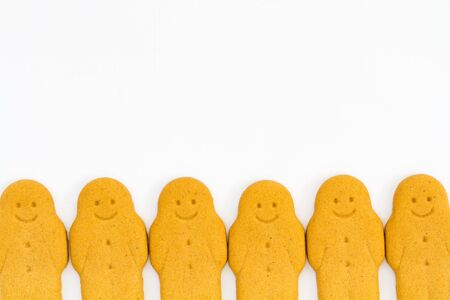 cheery: A row of Gingerbread Men smiling and looking happy at the bottom of the frame and on an isolated white background.