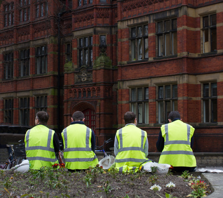 high visibility: YORK, UK - CIRCA MARCH, 2016. Construction workmen taking a break at lunchtime in their high visibility clothing and sitting outdoors on the streets of York, UK. Editorial