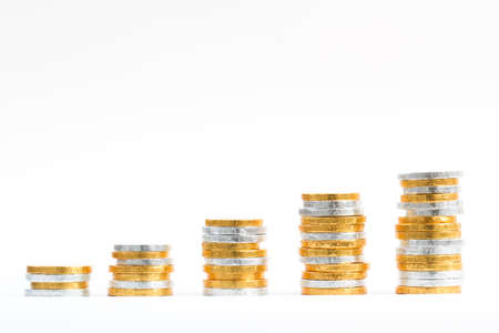 upward: Gold and silver coins on an isolated white background and in the shape of an upward growth graph.