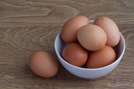 speckle: A white bowl full of fresh, brown, speckled eggs on a wooden table.