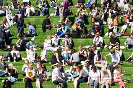 workmates: KNGS CROSS, LONDON, UK - MAY 5, 2016. Crowds of friends, family, colleagues and workmates enjoying the summer sunshine during a lunch break on a grassy hill at Kings Cross in the city of London.