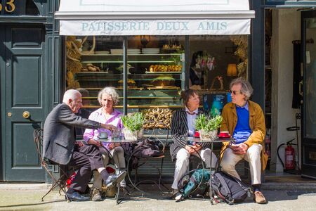 sightseers: PARIS, FRANCE - MAY 5, 2016. Elderly tourists sitting at the outdoor tables of a small French patisserie or cafe on the streets of Paris.