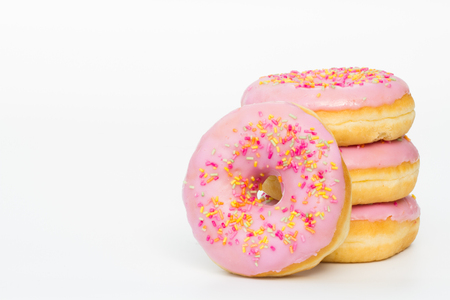 overeat: A stack of doughnuts with pink icing and sprinkles on an isolated white background.