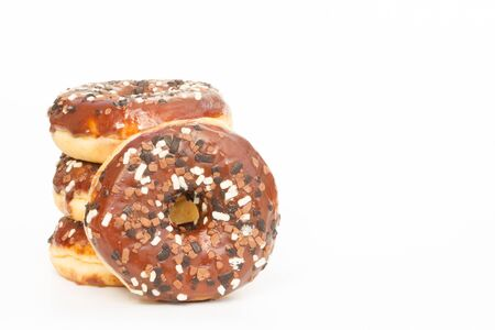 overeat: A stack of doughnuts with chocolate icing and sprinkles on an isolated white background.
