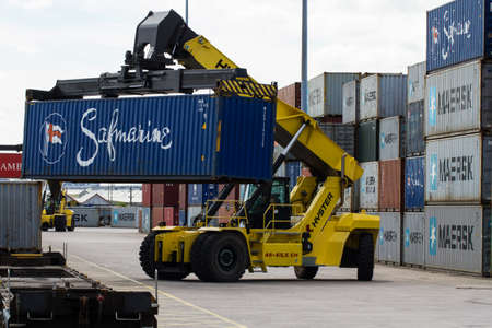 onward: DONCASTER, YORKSHIRE, UK - JULY 30, 2016. A heavy lifting machine loading and stacking a freight train with cargo and shipping containers in Doncaster Rail Port for onward movement to docks in the UK ready for export. Editorial