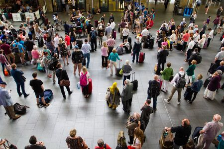 concourse: KINGS CROSS, LONDON, UK - JULY 21, 2016. Crowds of passengers, commuters and travellers waiting patiently in the concourse of Kings Cross railway station for information about their trains.