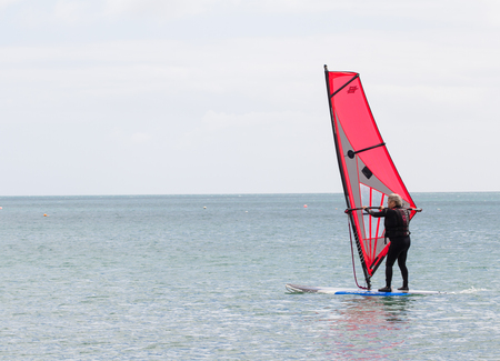 CORNWALL, UK - JULY 2, 2016. An elderly windsurfer keeping active in a wetsuit and sailing on a calm, flat ocean in Cornwall, UK.