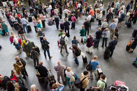 overcrowded: KINGS CROSS, LONDON, UK - JULY 21, 2016. Crowds of passengers, commuters and travellers waiting patiently in the concourse of Kings Cross railway station for information about their trains.