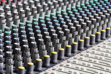 controls: The complex buttons, knobs and controls of an audio or sound engineer on a mixing board. Stock Photo