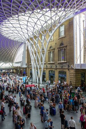 concourse: KINGS CROSS, LONDON, UK - JULY 21, 2016. The concourse of Kings Cross train station in London at rush hour and packed with passengers, commuters and travellers waiting for information about their trains under the elaborate, architectural mesh roof. Editorial