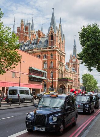 KINGS CROSS, LONDON, UK - JULY 21, 2016. Black London taxis queueing on the Euston Road with the Gothic architecture of St Pancras International train station in the background.
