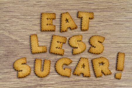 stating: Healthy eating advice stating eat less sugar and made from alphabet shaped cookies or biscuits on a wooden table.