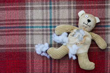A sad and damaged teddy bear with stuffing and filling falling from its ripped and torn tummy and waiting to be stitched and repaired on a seamstresses table.