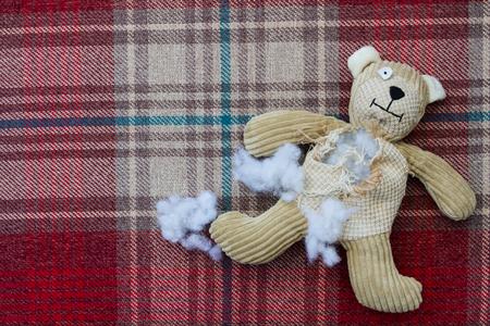 Eine traurige und beschädigt Teddybär mit Füllung und Füllung aus seiner zerrissenen und zerrissen Bauch fallen und warten genäht und auf einer Näherin Tisch repariert werden.