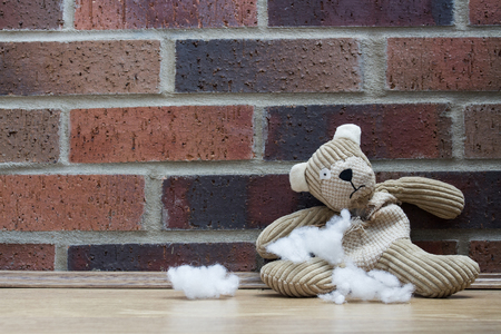 A sad and abandoned teddy bear sitting alone against a brick wall with stuffing and filling falling out of his ripped and torn tummy.