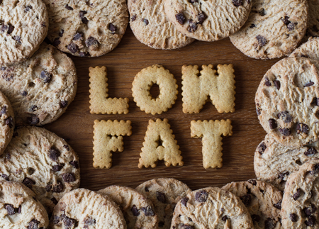 low fat: The phrase Low Fat spelled out with alphabet shaped cookies and surrounded by chocolate chip biscuits on a wooden background. Healthy eating advice. Stock Photo