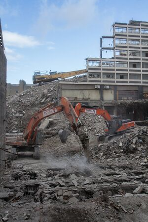 inner city: Two heavy plant machines demolishing inner city buildings on a demolition site that looks like a war zone.
